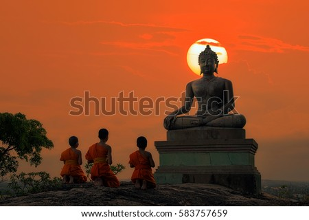 Novice monks chanting in front of Buddha statue