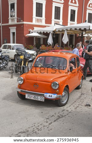NOVIGRAD, CROATIA - SEPTEMBER 13, 2014: Unrecognizable people watch the parade of vintage cars on the narrow streets on 5th International Old Timer Car Rally organized by club Eppur si muove from Umag - stock photo