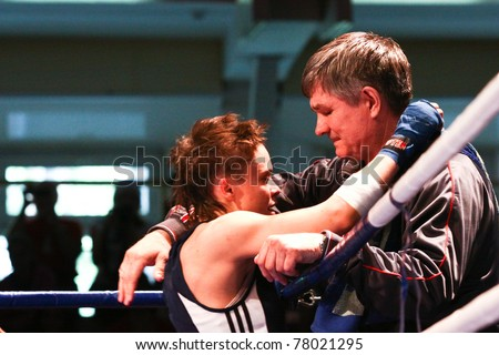NOVOSIBIRSK - MAY 21: Russian Championship in women's boxing. The after final battle   Gladkova Olesya(blue) and her coach winner Champion. May 21, 2011, Novosibirsk Russia