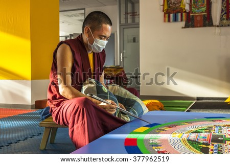 NOVOSIBIRSK - 13 November 2015: Tibetan monk making sand mandala, Kalachakra Mandala in Novosibirsk, Russia - stock photo