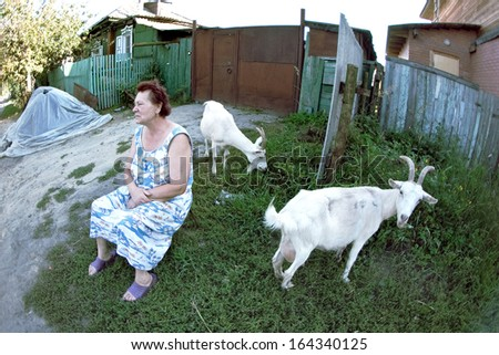 NOVOSIBIRSK REGION, RUSSIA - SEPTEMBER 2: A woman sits and thinks about something in the garden of her house, and it is a goat eating grass, September 2, 2011 in Novosibirsk Region, Russia