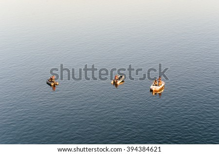 Novosibirsk, Russia - March 21, 2016: Unknown men involved in fishing from boats in Novosibirsk on 21 March 2016.