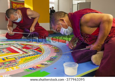 NOVOSIBIRSK, Russia - 13 November 2015: Buddhist monk making sand mandala Kalachakra. - stock photo