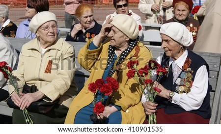 NOVOURALSK, RUSSIA - MAY, 9. Old women - veterans of the great Patriotic War with medals and bouquets of carnations on May 9, 2012 in city Novouralsk, Sverdlovsk region, Russia.