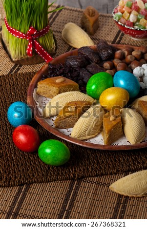 Novruz in Azerbaijan. Colored eggs for easter and traditional sweets. Selective focus. - stock photo