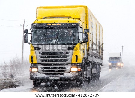 NOVYY URENGOY, RUSSIA - APRIL 28, 2013: Semi-trailer truck Scania G400 at the interurban road during a heavy blizzard. - stock photo