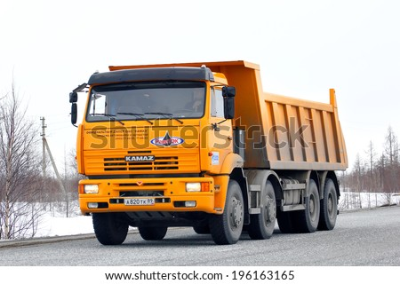 NOVYY URENGOY, RUSSIA - APRIL 23, 2013: Yellow KAMAZ 65201 dump truck at the interurban road. - stock photo