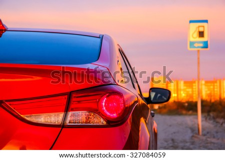 NOVYY URENGOY, RUSSIA - AUGUST 30, 2015: Backlight of the motor car Hyundai Elantra at the background of the sunset and the gas station road sign. - stock photo