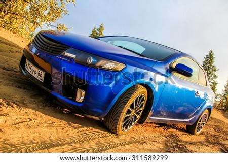 NOVYY URENGOY, RUSSIA - AUGUST 30, 2015: Motor car Kia Cerato Koup at the countryside. - stock photo