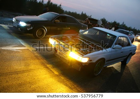 NOVYY URENGOY, RUSSIA - AUGUST 12, 2016: Motor cars Nissan Laurel and Toyota Mark II takes part in the night street drag racing.