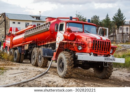 NOVYY URENGOY, RUSSIA - AUGUST 3, 2015: Red fire cistern Ural 44202 takes part in the extinguishing of a fire in an old wooden house. - stock photo