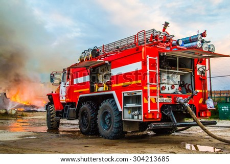NOVYY URENGOY, RUSSIA - AUGUST 3, 2015: Red firetruck Ural 5557 takes part in the extinguishing of a fire in an old wooden house. - stock photo