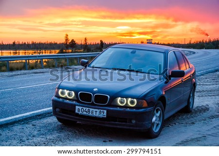 NOVYY URENGOY, RUSSIA - JULY 25, 2015: Business class sedan BMW E39 520i at the background of the sunset. - stock photo