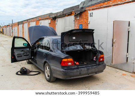 NOVYY URENGOY, RUSSIA - JUNE 26, 2015: Motor car BMW E39 520i is washed and cleaned near the garage. - stock photo
