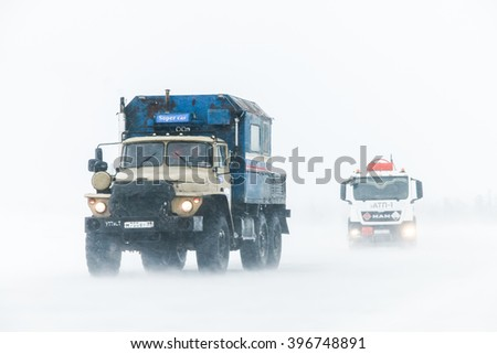 NOVYY URENGOY, RUSSIA - MARCH 20, 2016: Truck Ural 4320 at the interurban freeway during a heavy northern blizzard. - stock photo