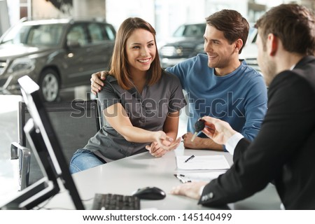Now her dream comes true. Car salesman giving the key of the new car to the young attractive owners - stock photo