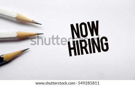 Now hiring memo written on a white background with pencils