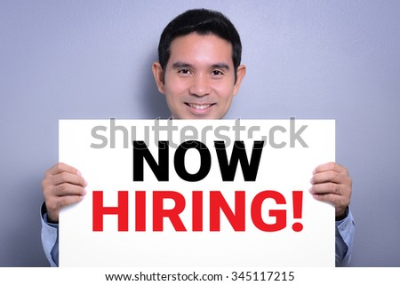 NOW HIRING, message on white cardboard held by smiling man