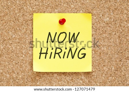 Now Hiring written on an yellow sticky note pinned with red push pin on cork bulletin board. - stock photo