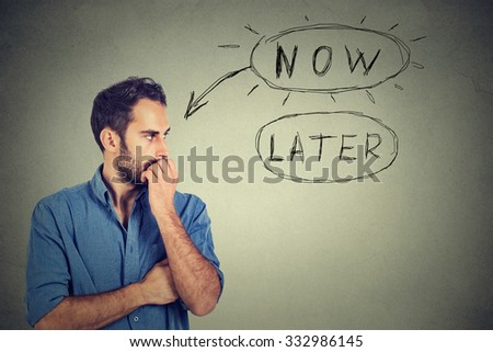 Now or later. Man thinking biting his fingernails looking worried anxious making up his mind isolated on grey wall background. Human face expression - stock photo