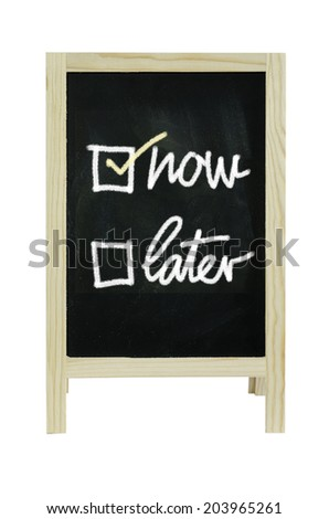 Now or Later with checkboxes - white chalk handwriting on blackboard Clipping path