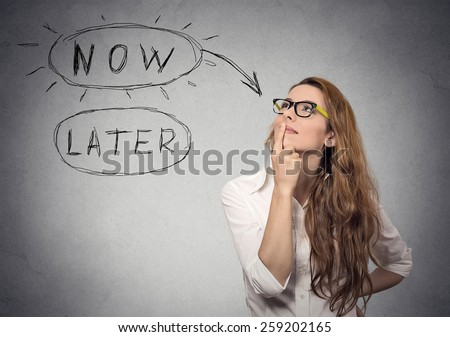 Now or later. Woman thinking looking up isolated on grey wall background. Human face expression  - stock photo