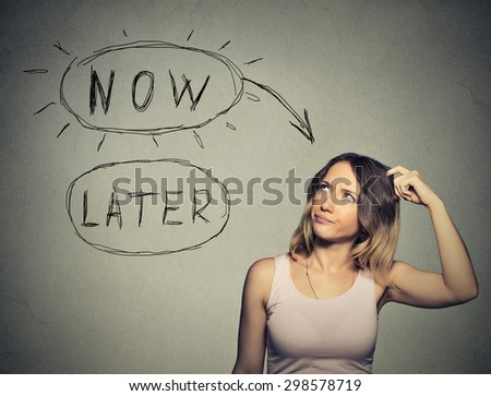 Now or later. Woman thinking scratching head looking up isolated on grey wall background. Human face expression - stock photo