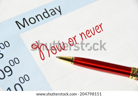Now or never note in the agenda - stock photo