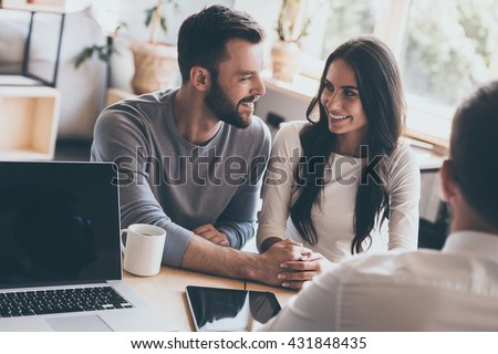 Now they feel happy. Happy young loving couple bonding to each other and looking at each other while sitting together with their financial advisor - stock photo