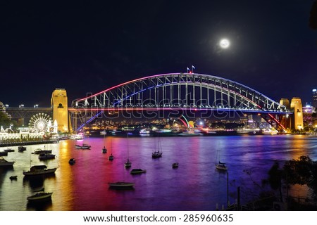 NTH SYDNEY, AUSTRALIA - JUNE 6, 2015;  Scenic views across Lavender Bay, Sydney Harbour to  Sydney Harbour Bridge and Sydney Opera House and city buildings during Vivid Sydney - rainbow colours - stock photo