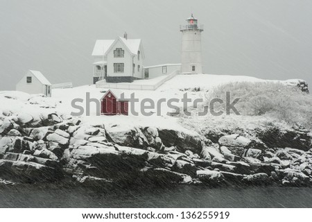 Nubble lighthouse in a Maine coastal snowstorm. - stock photo