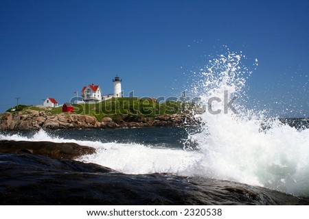 Nubble lighthouse with wave - stock photo