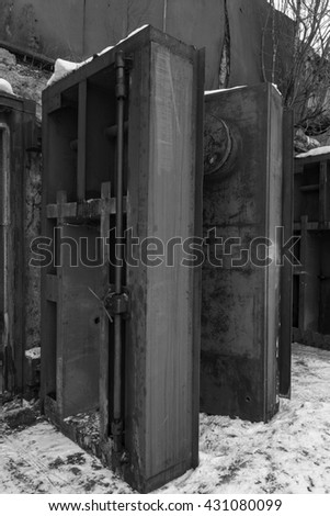 Nuclear bunker. Nuclear bomb shelter. Old abandoned Soviet Cold War bunker in forest. Upcoming reinforced steel hopper gates. Black and white photo.