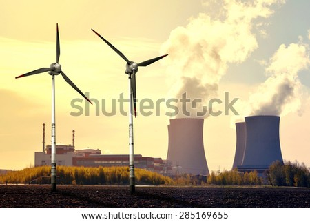 Nuclear power plant and wind turbines at sunset - Green energy concept - stock photo