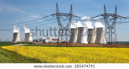 Nuclear power plant Dukovany with golden glowering field of rapeseed - Czech Republic - two possibility for production energy - stock photo