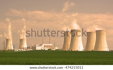 Nuclear power plant. Giant cooling towers with vapor. Nuclear power production concept. Wide panoramic view.
