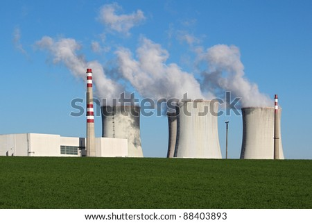nuclear power plant in green field - stock photo