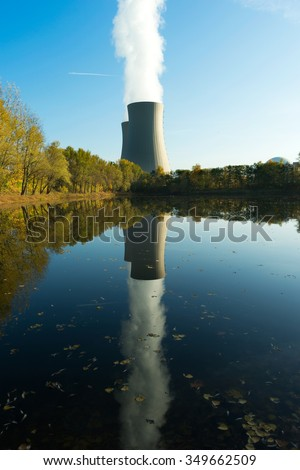 Nuclear power plant next the pond and its reflection in the water - stock photo