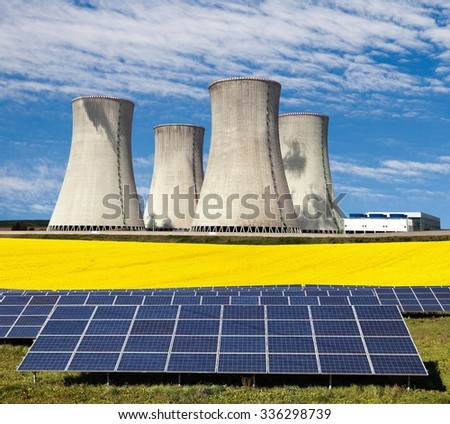 Nuclear power plant with golden glowering field of rapeseed and photovoltaic sunny power plant - Three possibility for production of electric energy - stock photo