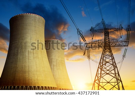 Nuclear power plant with high voltage towers against the sunset - stock photo
