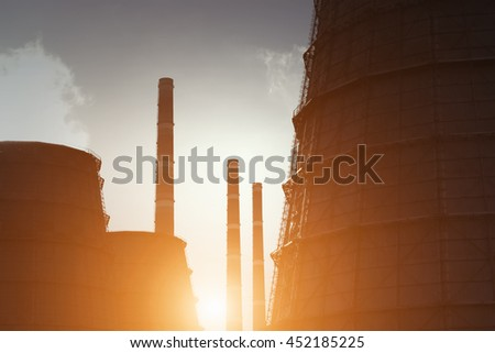 Nuclear power plant with pipes at sunset - stock photo