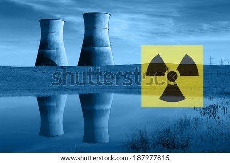 Nuclear reactor cooling towers in blue, reflected in pond, and international nuclear radiation hazard symbol.