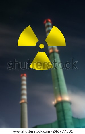Nuclear symbol at Blurred Silhouette of Nuclear Power Plant background - stock photo