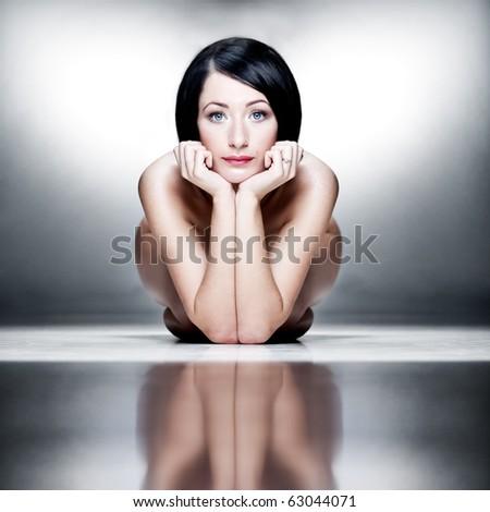 Nude artistic portrait of a caucasian woman on studio floor - stock photo