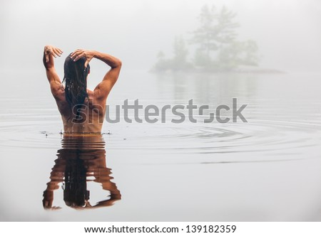 Nude back of middle aged Caucasian woman bathing  and washing hair in Maine lake on a foggy Summer morning. - stock photo