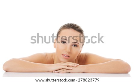 Nude blonde woman posing with arms on desk. - stock photo