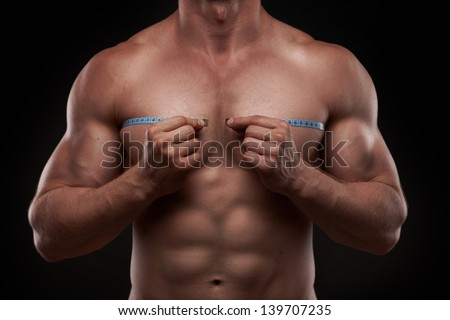 Nude bodybuilder with a measuring tape around his chest isolated on black background - stock photo