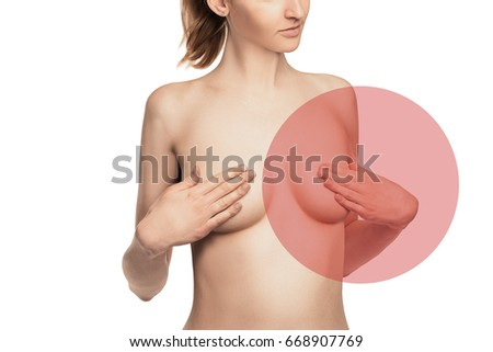 nude Female breast. Young caucasian adult woman examining her breast for lumps or signs of breast cancer with red sign of disease. Isolated white background
