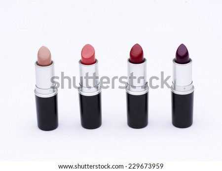 nude fuchsia red violet lipstick for outgoing woman with black and silver case isolated in white background  - stock photo