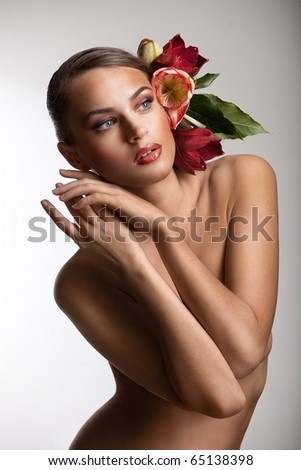 Nude girl with flowers in her hair on the grey background - stock photo
